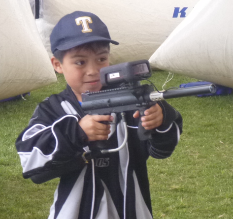 Young child pointing laser gun during laser tag game Lima, Peru